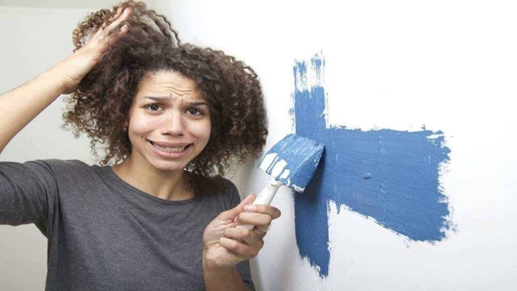 Stressed woman painting her house